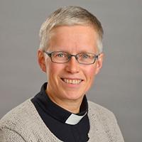 Kvinna med grå tröja och svart prästskjorta