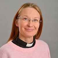 Kvinna med rosa tröja och svart prästskjorta